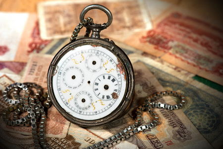 hands in pocket: Broken pocket watch with chain and without clock hands on the old paper banknotes Stock Photo