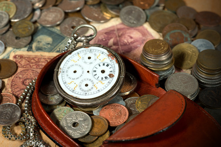 Leather purse with old coins, paper banknotes and a broken pocket watch without clock hands