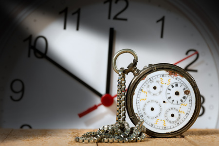 Old and vintage broken pocket watch with silver chain with a modern clock on the background