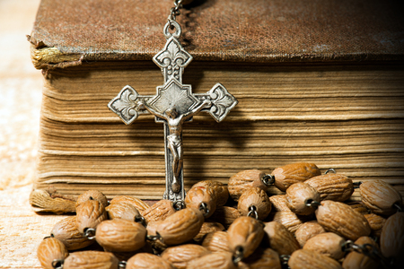 viernes santo: Detail of an old silver crucifix and rosary with wooden beads. On a wooden table with an old Holy Bible