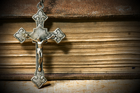 Detail of a silver small crucifix with an old Holy Bible with dark shadows on a wooden table Stock Photo
