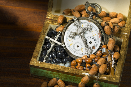 Time to pray - Open wooden box full of rosary beads, crucifixes and an old pocket watch with a vintage silver crucifix