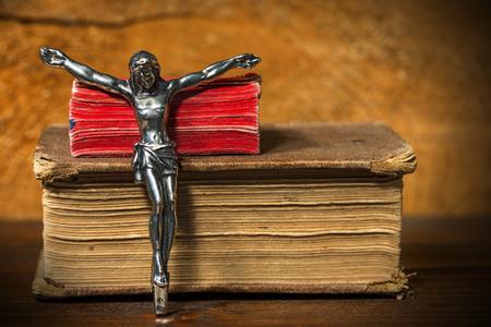 viernes santo: Crucifijo de plata sin la cruz y dos Sagradas Biblias en una mesa de madera con sombras oscuras