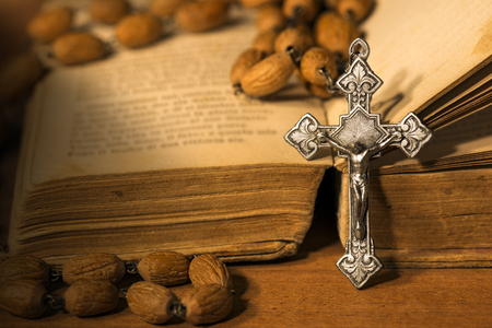 Silver crucifix and rosary with wooden beads on a old Holy Bible on a wooden table with dark shadows
