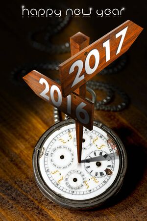 Happy New Year 2017 - Old pocket watch with two wooden signs with arrows and the years 2016 and 2017