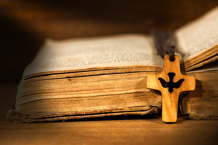 vangelo aperto: Small wooden crucifix with a dove and rope on an old Holy Bible