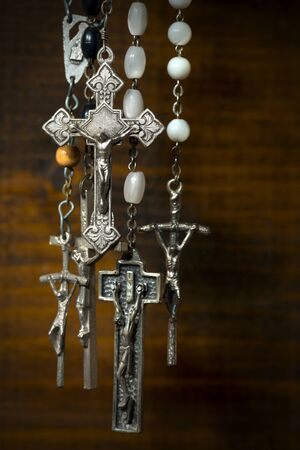crucifixes: Detail of a group of silver crucifixes with rosary beads. Hanging on a wooden background with dark shadows Stock Photo