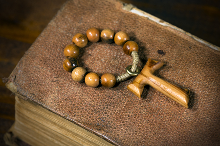 Tau, wooden cross in shape of the letter t (religious symbol of St. Francis of Assisi) with rosary bead on an old Holy Bible