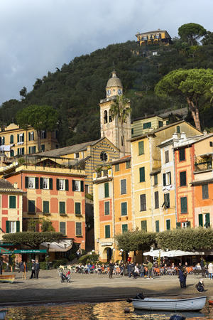PORTOFINO, ITALY - DECEMBER 9, 2016: People in the square of the village of Portofino with the colorful houses and the church of St. Martin. Genova, Liguria, Italy
