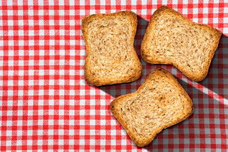 galletas integrales: Tres bizcochos de harina integral saludables en una mesa con mantel a cuadros rojo y blanco