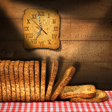 rusk: Rusks of wholemeal flour on a table with red and white checkered tablecloth with a clock made with a rusk. Concept of time for a healthy breakfast
