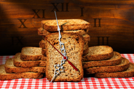 rusk: Rusks of wholemeal flour on a table with a clock made with a rusk. Concept of time for a healthy breakfast