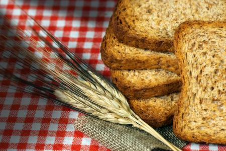 galletas integrales: Detalle de bizcochos sanas de harina integral sobre una mesa con mantel y espigas de trigo cuadros rojos y blancos