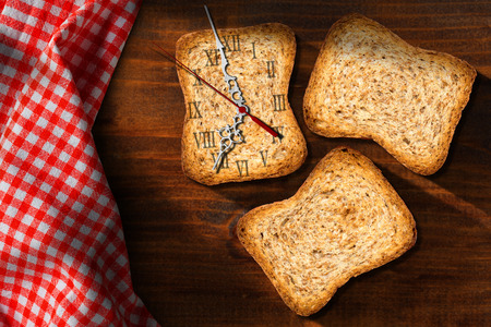 Three healthy rusks of wholemeal flour with a clock made with a rusk. Concept of time for a healthy breakfast Stock Photo