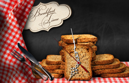 Rusks on a table with a clock made with a rusk, silver cutlery and a label with text Breakfast time Stock Photo