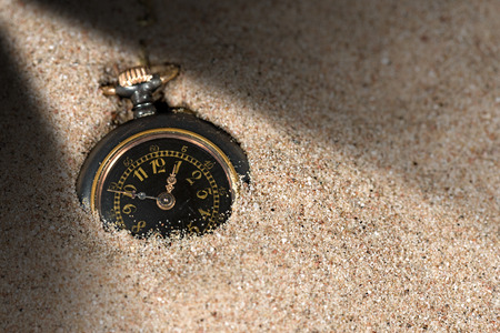 sand watch: Detail of an old and small pocket watch partially buried in the sand