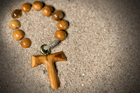 Tau, wooden cross in the shape of the letter t (symbol of St. Francis of Assisi) with rosary bead partially buried in the sand
