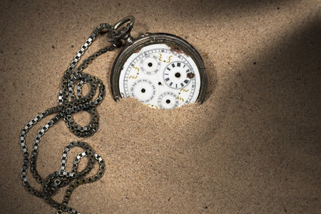 partially: Old and broken pocket watch with chain and without watch hands partially buried in the sand