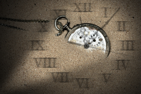 partially: Broken pocket watch with shadows of clock hands and roman numbers partially buried in the sand