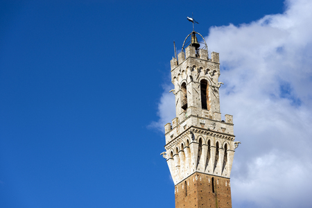 Detail of the Torre del Mangia 87 m. (Tower of Mangia) on blue sky with clouds. Siena, Toscana (Tuscany), Italy