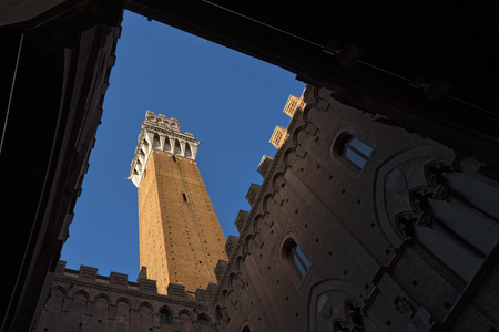 Torre del Mangia 87 m. bottom view (Tower of Mangia) on blue sky with clouds. Siena, Toscana (Tuscany), Italy Editorial