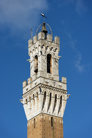 Detail of the Torre del Mangia 87 m. (Tower of Mangia) on blue sky. Siena, Toscana (Tuscany), Italy