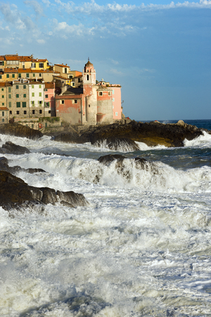 mare agitato: Tellaro village with the Church of St. George (San Giorgio), with cliffs and rough sea. La Spezia, Liguria, Italy