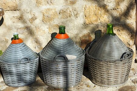 Three wine demijohns in an old village in Tuscany, Italy, Europe
