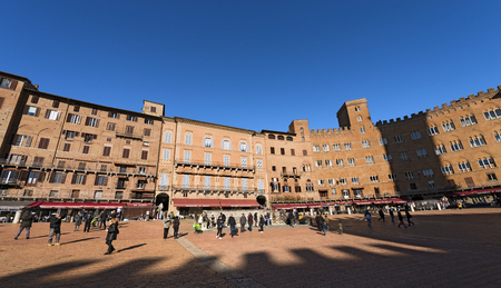 SIENA, ITALY - JANUARY 5, 2017: Many tourists visit the ancient and medieval Piazza del Campo (Campo square) in the downtown of Siena, Toscana (Tuscany), Italy