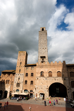 SAN GIMIGNANO, ITALY - JULY 12, 2014: Tourists visit the ancient and medieval Piazza del Duomo, (Cathedral square). San Gimignano (UNESCO heritage), Siena, Tuscany, Italy Editorial