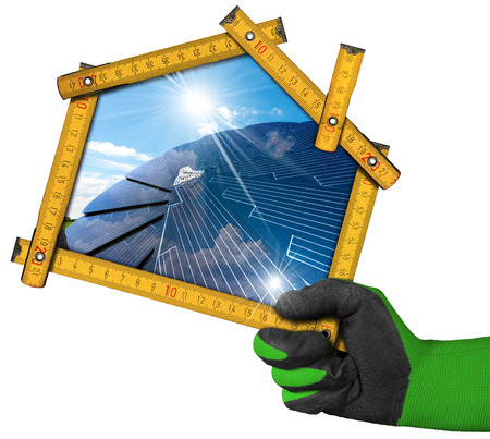 Hand with work glove holding a wooden ruler in the shape of house with a solar panel and sun rays inside. Concept of ecological house
