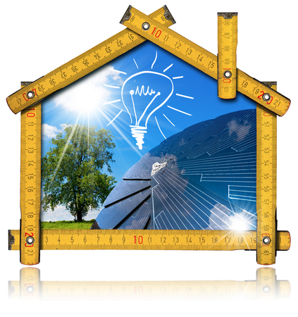 electricity meter: Wooden ruler in the shape of ecologic house with a solar panel, light bulb, blue sky, tree and sun rays. Concept of ecological house