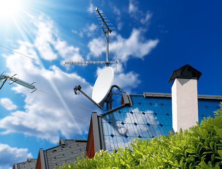 parabolic mirror: Close-up of a house roof with solar panels and satellite dish with antenna TV,  on a blue sky with clouds, sun rays and a power line