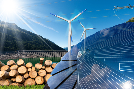 Renewable energies sources - Wind energy (wind turbines),  solar energy (solar panels), biomass (tree trunks) and hydropower (dam for hydroelectric power) Stock Photo