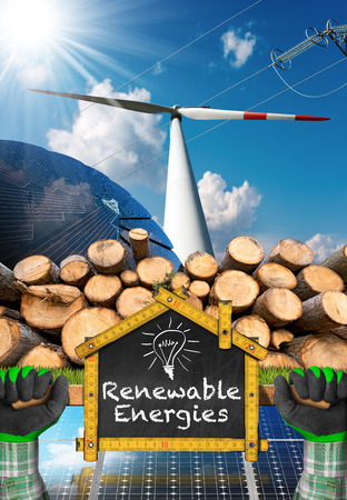 Renewable energies sources - Wind energy with a wind turbine, solar energy with a solar panels, biomass with a stack of tree trunks Stock Photo