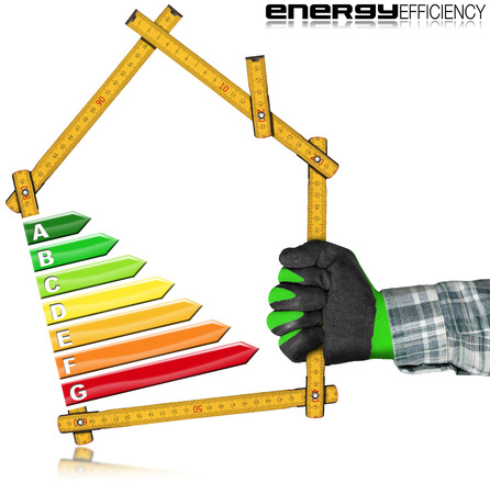 Energy Efficiency - Hand with work glove holding a wooden folding ruler in the shape of house with energy efficiency rating. Isolated on white background Stock Photo
