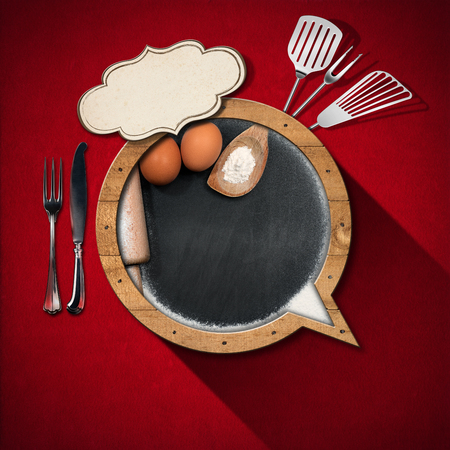 Blackboard and label with copy space in the shape of speech bubble with flour, eggs, rolling pin, kitchen utensils and silver cutlery on a red velvet background