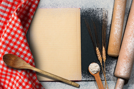 Empty recipe book with lined paper on a baking background with flour, ears of wheat, wooden kitchen utensils and a checkered tablecloth