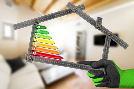 rating: Energy Efficiency - Hand with work glove holding a metal ruler in the shape of house with energy efficiency rating. Home interior Stock Photo