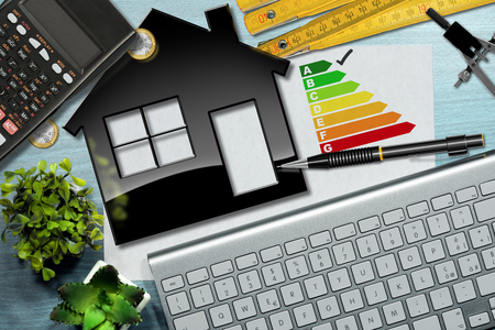 rating: Energy efficiency rating graph on a desk with a house model, calculator, folding ruler, drawing compass, pencil and a computer keyboard Stock Photo