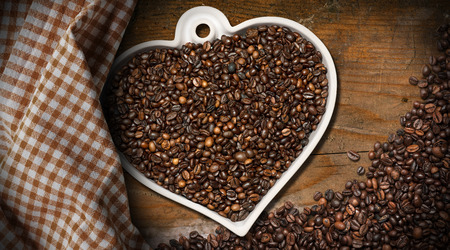 heart shaped: Roasted coffee beans in a heart shaped bowl, on a wooden table with a checkered tablecloth. Love Coffee concept