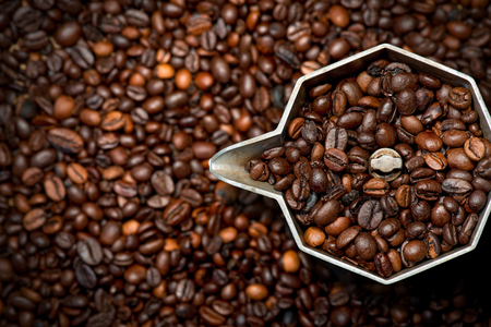 aluminium: Closeup of an old italian coffee maker (moka pot - top view) with roasted coffee beans inside and on background Stock Photo