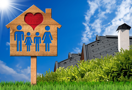 Unterzeichnen Sie in Form eines hölzernen Musterhauses mit einer Familie und einem roten Herzen. Auf grünem Gras mit zwei Dächern von Häusern Standard-Bild - 87941685