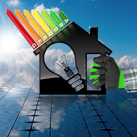 Hand with work glove holding a symbol in the shape of house with energy efficiency rating and a light bulb (3D illustration) on a solar panel and sky (photo)
