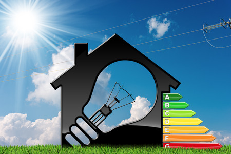 Energy Efficiency - 3D illustration of a model house with a light bulb and energy efficiency rating on green grass with blue sky, clouds, sun rays and a power line Stock Photo
