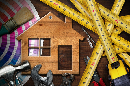 Home improvement concept - Wooden model house on a work table with tools 스톡 콘텐츠
