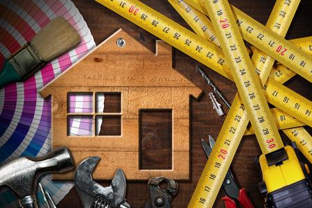 Concepto de mejoras para el hogar - Casa modelo de madera sobre una mesa de trabajo con herramientas Foto de archivo