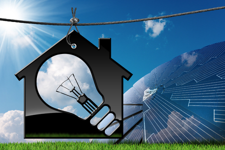 3D illustration of a model house with a light bulb on a blue sky with clouds, sun rays and a solar panel (photo) - Renewable energies concept Stock Photo