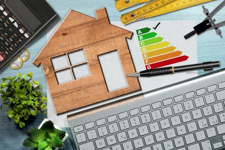 Gráfico de avaliação de eficiência de energia em uma mesa com um modelo de casa de madeira, calculadora, régua de dobradura, desenho de bússola, lápis e um teclado de computador Foto de archivo