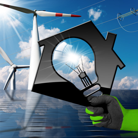 Hand with work glove holding a model house with a light bulb, solar panel (3D illustration), wind turbines and a power line on a blue sky with clouds (photo) - Renewable energies concept Stock Photo